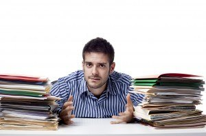 businessman with pile of files on his desk